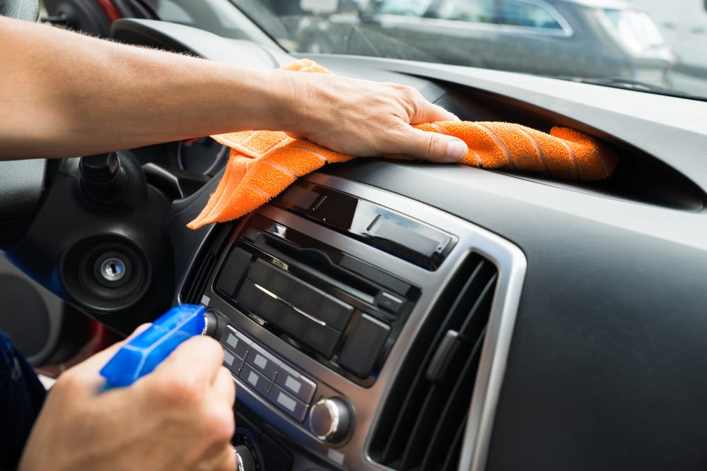 man is cleaning a car